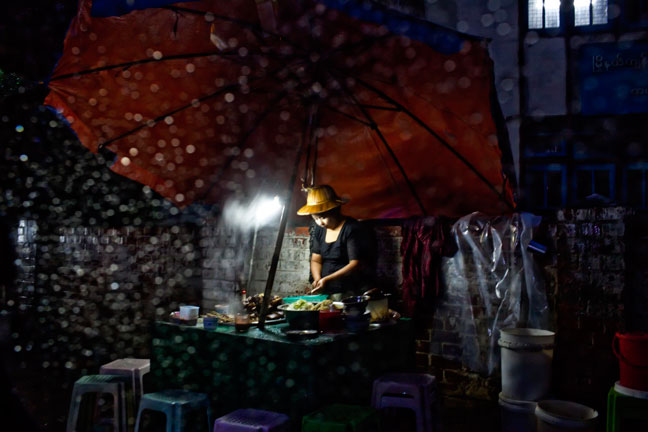 A street vendor sets up her stall on the rainy streets of Yangon, Myanmar.  Inquire about this image