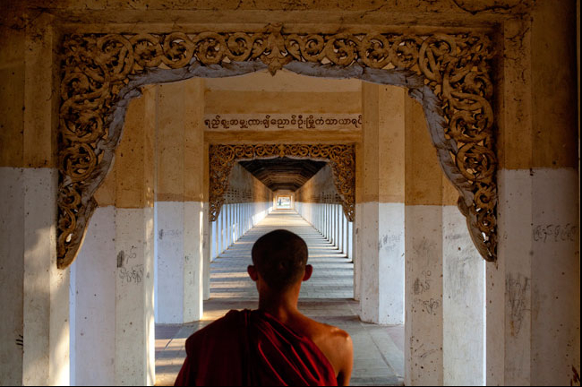 A portrait of a novice monk on his way to collect offerings near Bagan, Myanmar.  Inquire about this image