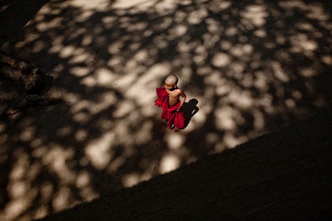 A novice monk tries to fix his robe after lunch at a local monastery in Bagan, Myanmar.  Inquire about this image