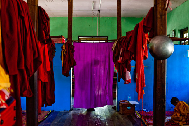 A novice monk fixes his robe in the dormitory of a local monastery near Lake Inle, Myanmar.  Inquire about this image
