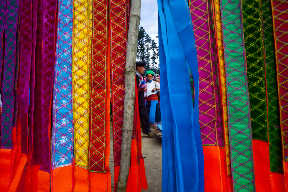 Stalls of clothing vendors sell colorful garments at the Xa Phin market.  About 10 kilometers from Dong Van down a windy road tucked away in the small village of Xa Phin is a bustling local ethnic minority market.  Inquire about this image