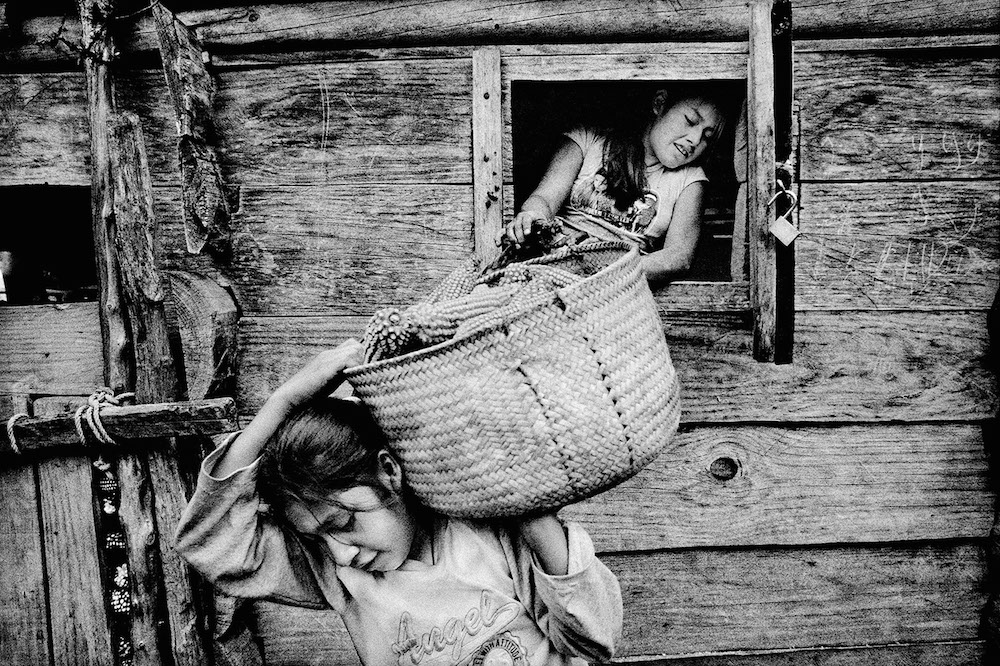 Sisters empty their family's corn crib. San Miguel Cuevas, Mexico. 2008.  Inquire about this image