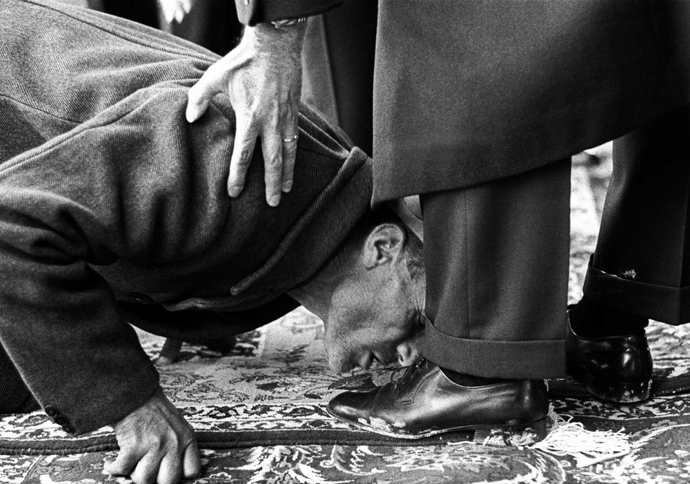 A peasant kisses the feet of Reza Palewi, the Shah of Iran, during a ceremony of distribution of land deeds.  Inquire about this image