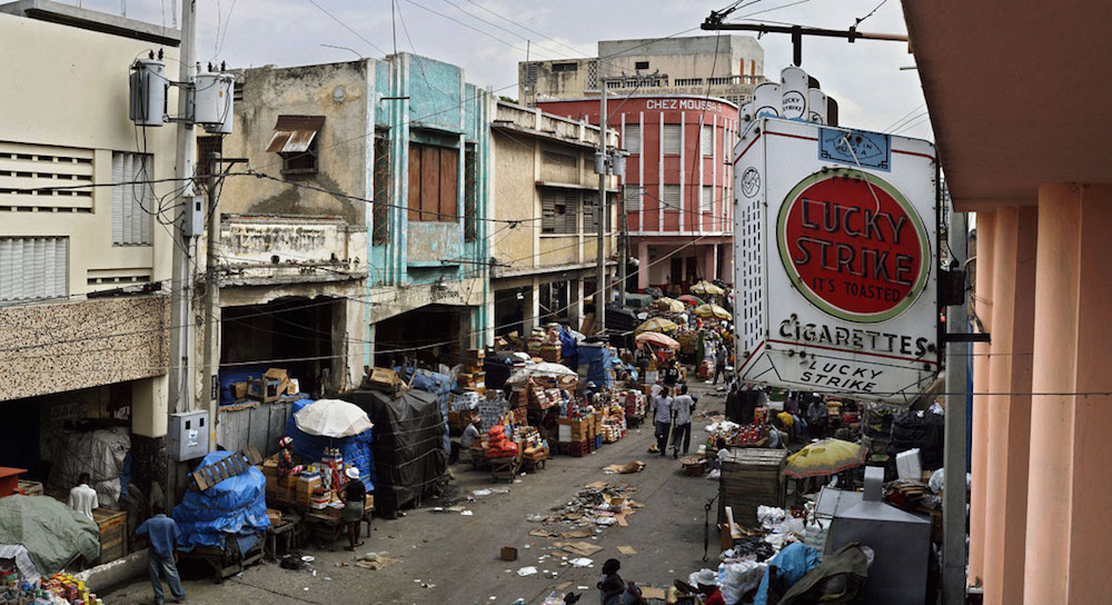 A scene in the old city of Port-au-Prince. Decaying Colonial architecture acts as the stage setting while the average Haitian struggles to scratch out a living during the country's downward spiral. February 9, 2006.  Inquire about this image