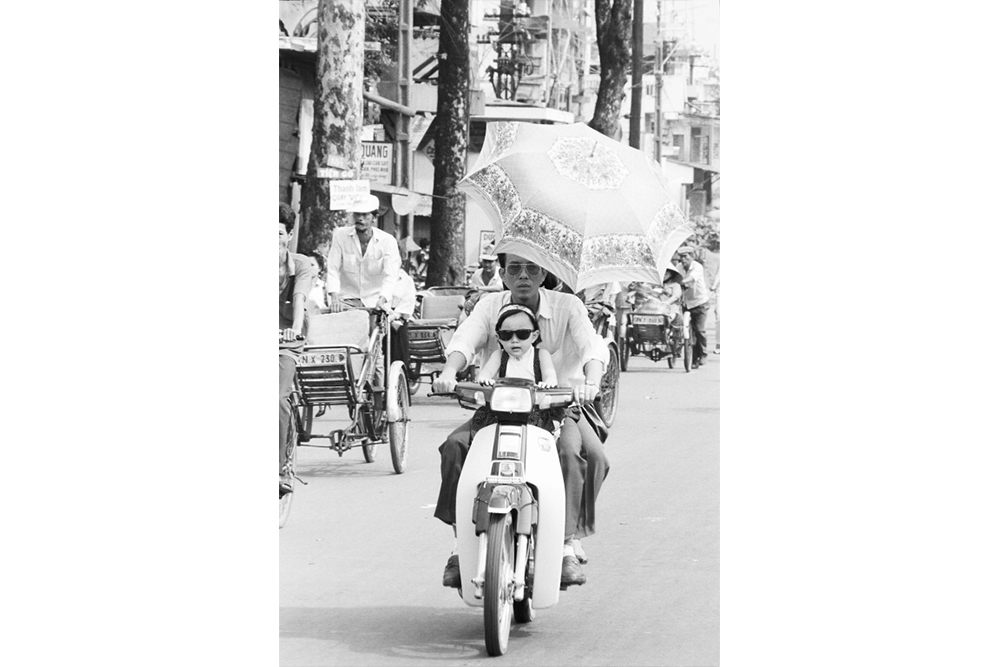 A father and daughter out for a Sunday ride, well protected from the harsh sun. 1994.  Inquire about this image