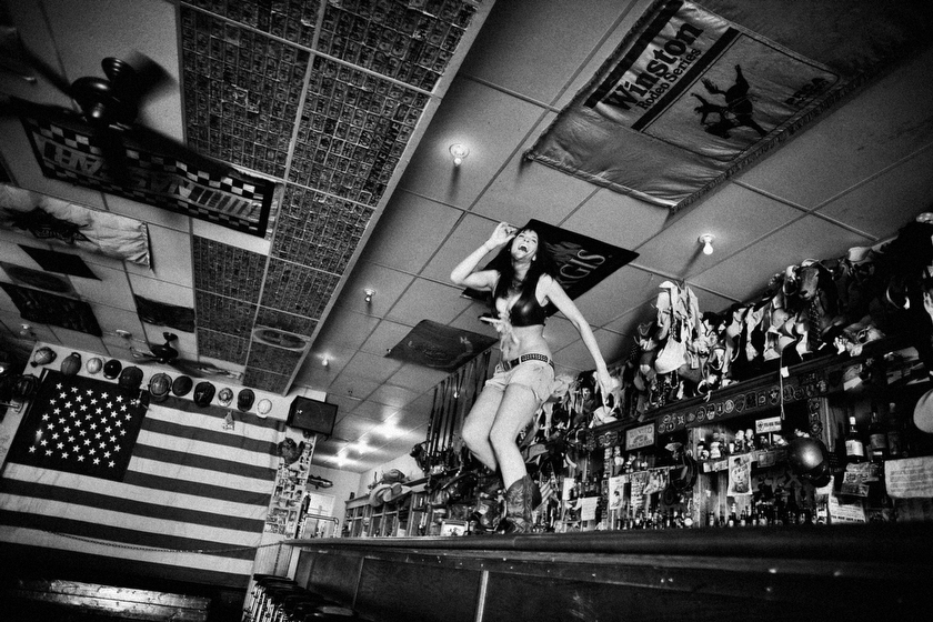 "Jasmin, a bartender at the Hogs and Heifers bar in downtown Las Vegas dances on the bar to try and drum up mid-day business. The movie ""Coyote Ugly,"" with its dancing girl bartender stars was inspired by the Hogs and Heifers bar.  Inquire about this image"