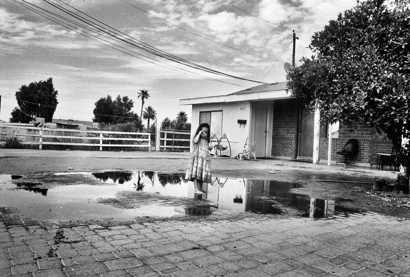 A young girl stands and cries in the desert heat of Arizona after her being hosed down with water in their front yard near Phoenix. The family could not afford air conditioning, so improvised the best they could to keep cool.  Inquire about this image