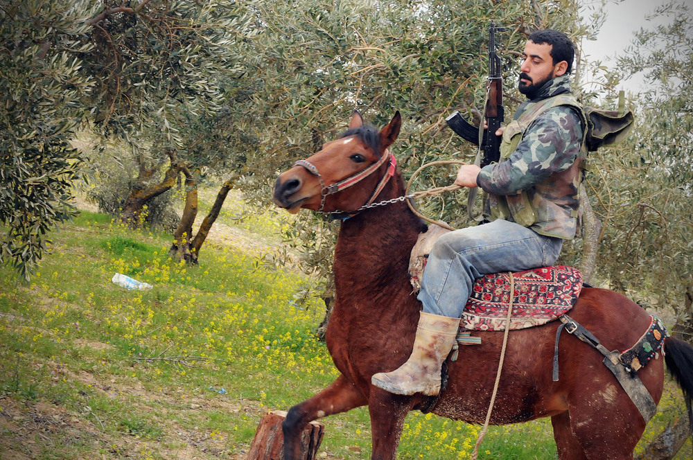 March 15, 2012: Al Shatouria, Syria. A FSA member is riding a horse during a retreat of his unit through to the mountains after their defeat inside the city of Idlib.  Inquire about this image
