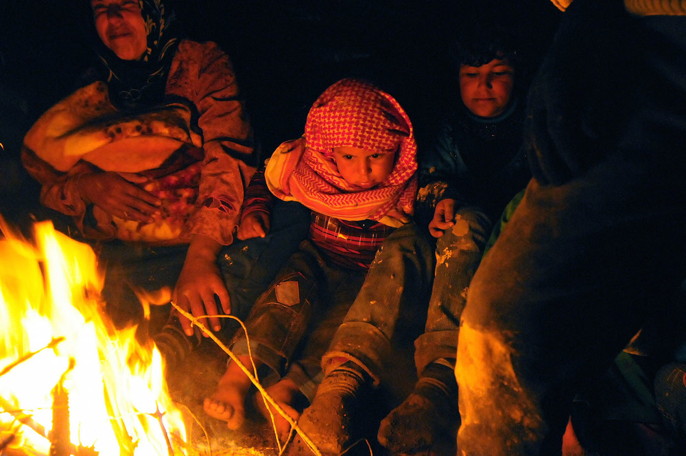 March 19, 2012: Turkish border, Syria. Syrian families fleeing the war zone are resting near a camp fire a few hundred meters from the Turkish border.   Inquire about this image