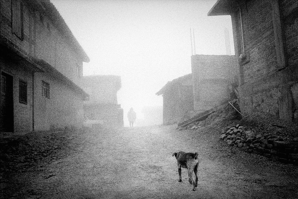 Late afternoon fog drifts through deserted streets. San Miguel Cuevas, Mexico. 2009.   Inquire about this image