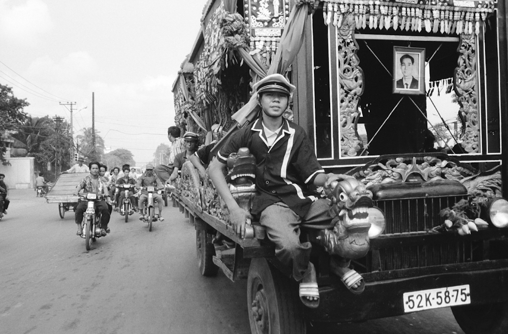 In what is almost a daily scene, a funeral procession wheels through the city on route to a cemetery on the outskirts of town. 1994.   Inquire about this image