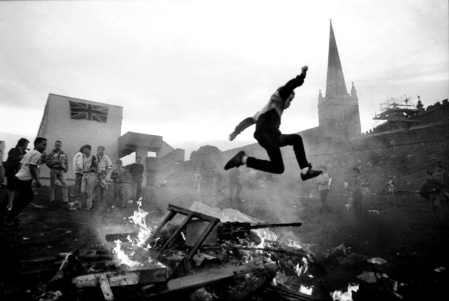 Protestant youth play around a bonfire in a working class housing estate in Derry, Northern Ireland. June 1989.   Inquire about this image