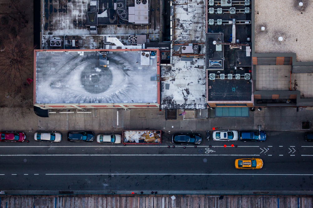A photographic installation by the artist JR adorns the roof of a building that used to tape The Colbert Report on West 54th Street. December 2014.  Inquire about this image