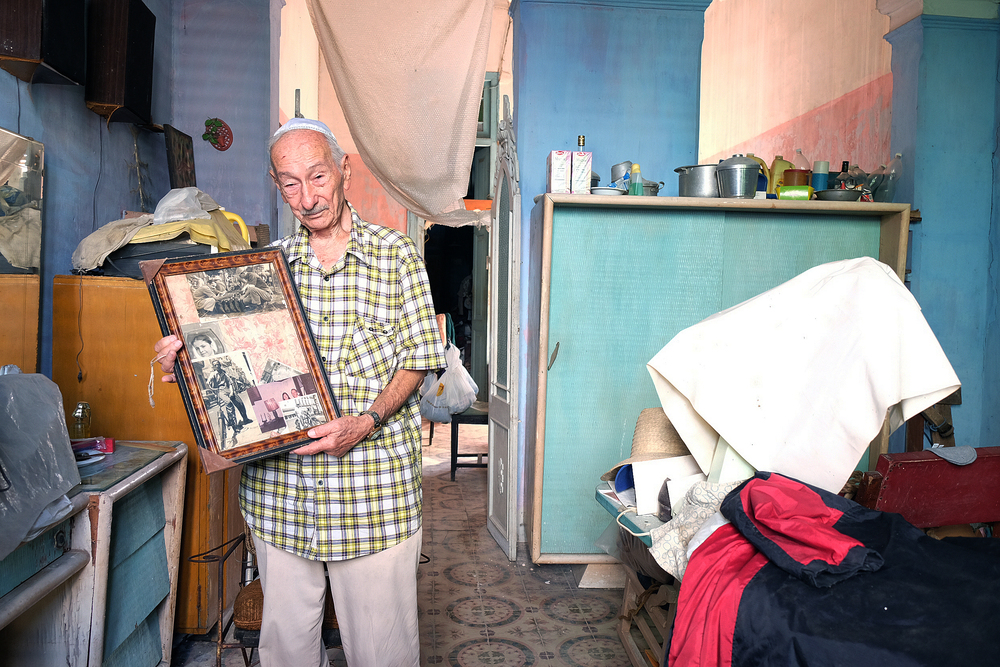 A member of the Sefarati Synagogue shows photographs of his parents.    Inquire about this image