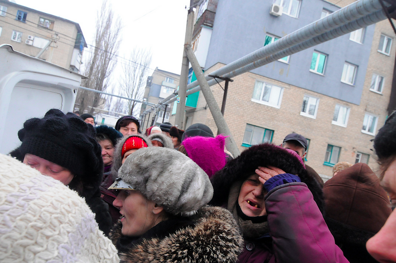 February 9, 2015, Debaltseve, Donbass Oblast, Ukraine. Locals are waiting in line get food as shells land near by.