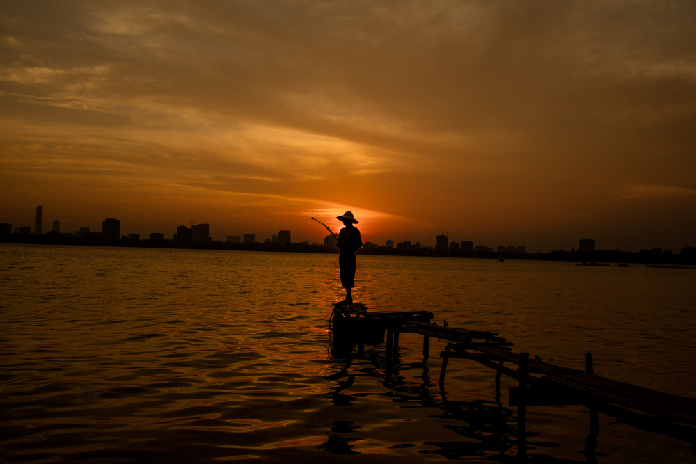 An urban fisherman takes in the last hours of daylight overlooking West Lake in Hanoi, Vietnam.   Inquire about this image