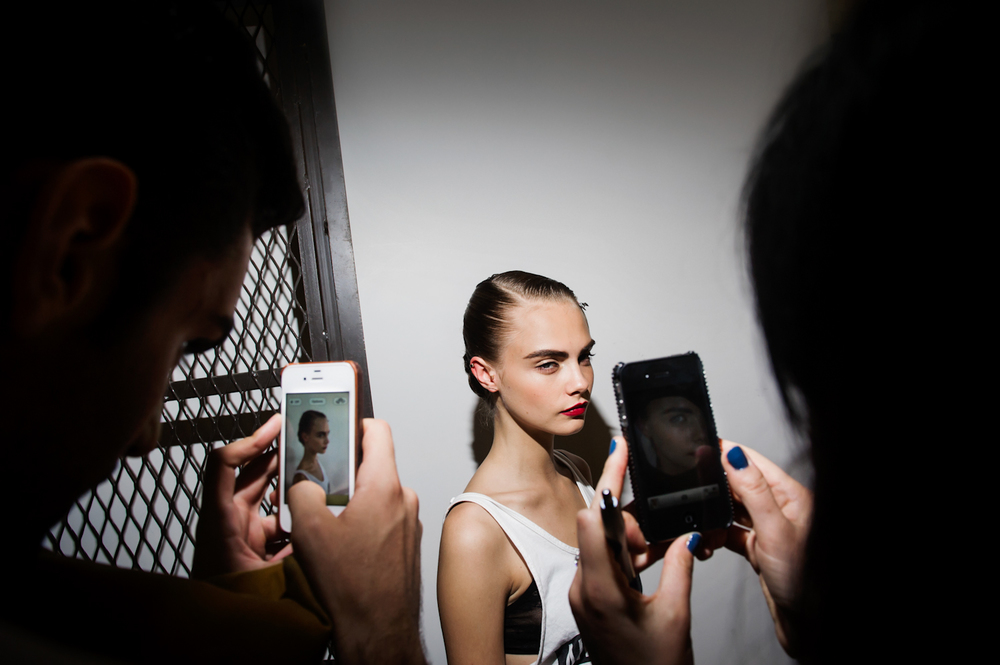 Model Cara Delevingne is photographed with iphones by her fans backstage at Jason Wu. New York Fashion Week, Spring 2013.  Inquire about this image