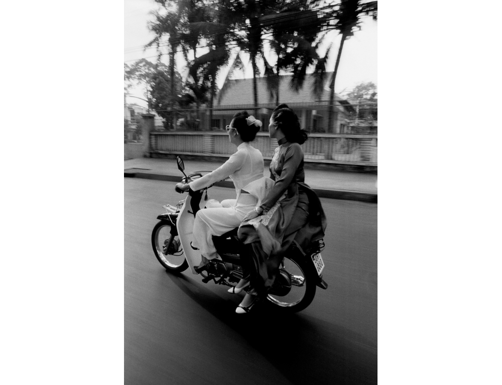 Except for the motorbike, these traditionally dressed women could be from another era of Saigon's stylish past. 1994.   Inquire about this image