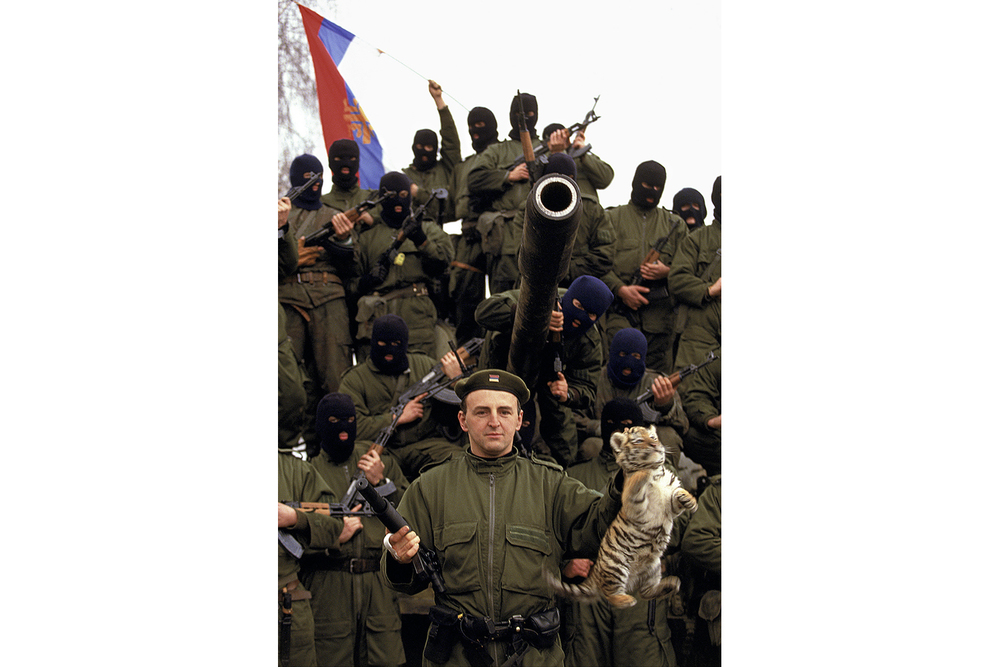 Serbian Tiger leader Zeljko Raznatovic or Arkan poses with his paramilitary unit, waving the Serbian flag, and a baby tiger that he liberated from a Croatian zoo in Erdut, Croatia, in the fall of 1991. Arkan's Tigers were responsible for a large part of the ethnic cleansing that occurred at the beginning of the war in Bosnia.  Inquire about this image