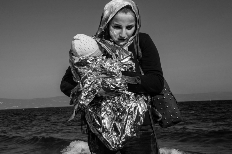 Lesbos Island, Greece, Nov. 16, 2015. A female refugee who has just crossed from Turkey holds her baby wrapped in thermal blankets. She traveled by rubber dinghy and landed with other members of her family on the northern shore of the island.