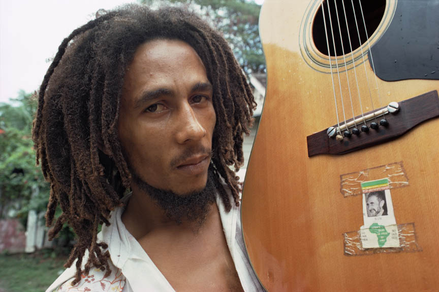 Bob Marley with his guitar, decorated with a picture of Haile Selassie at his home, Tuff Gong, Kingston, Jamaica, March 1976.  Inquire about this image