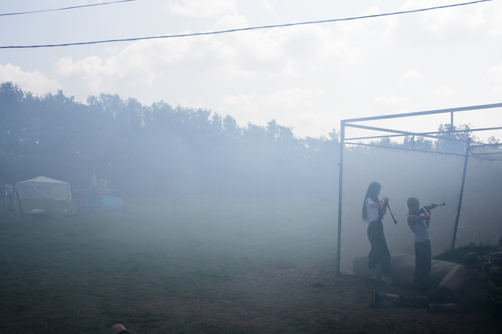 A fake grenade is launched, setting smoke in the atmosphere as students practice a drill with air-soft guns at the Historical-War Camp in Borodino, Russia.   Inquire about this image