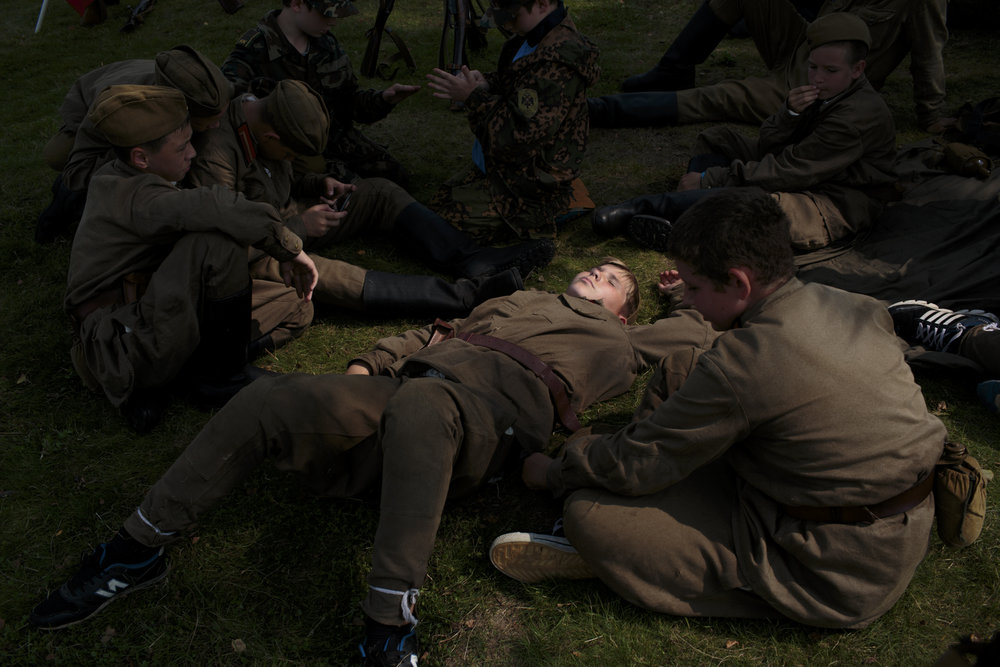 A unit dresses to re-enact Soviet Russia during WWII as part of their historical education in Borodino, Russia. The camp offers reenactments of historical periods of war.   Inquire about this image