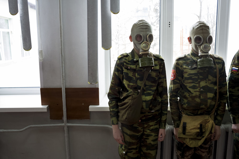Students stand ready as a teacher observes how quickly they can dress in gask masks at School #7 in Dmitrov, Russia.  Inquire about this image