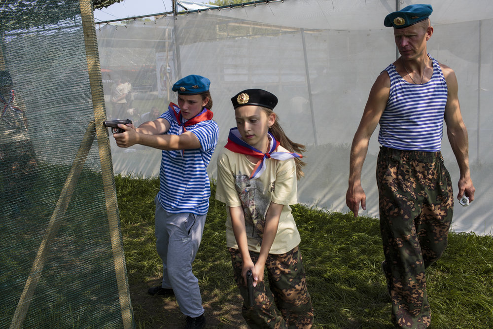Students dressed in traditional shirts and hats of the Russian air force participate in a fire-arm drill at Исторический Лагерь Бородино 2016, the Historical-War Camp in Borodino, Russia.   Inquire about this image