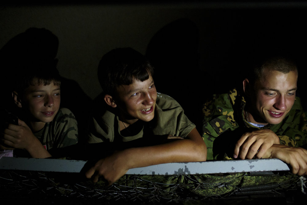 "Students from Stavropol rest in their tent before sleeping at camp. Without electricity, the students use their phones and flashlights to play games. ""Orthodox Warrior"" camp takes place in Diveevo, the center of pilgrimage for Orthodox Christians in Russia.  Inquire about this image"