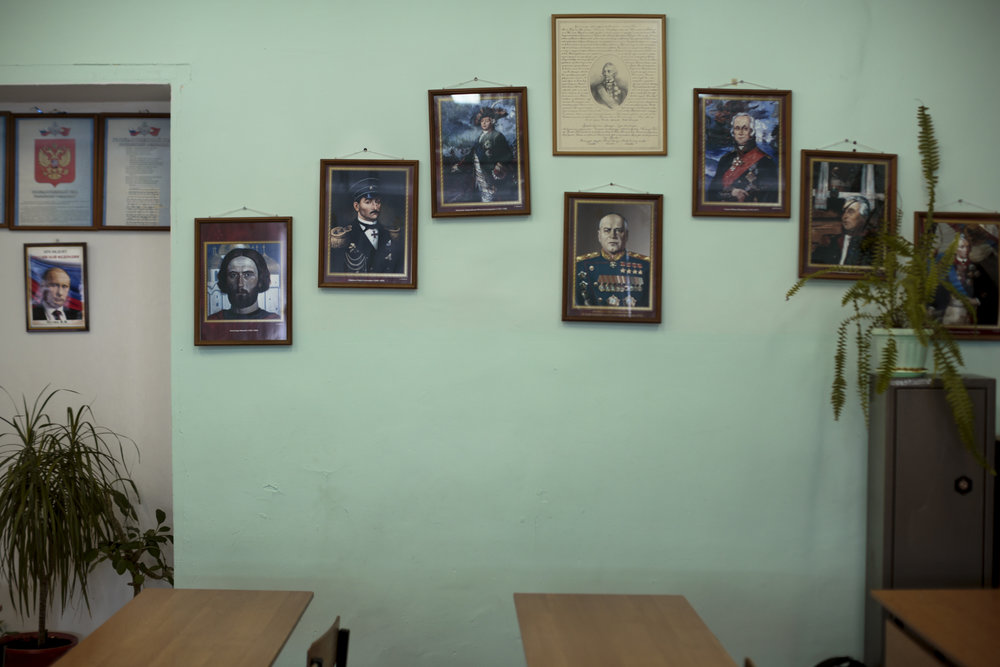 A wall is decorated with legacies from Russian history, starting with Vladimir Putin on the far left. School #7, Diveevo, Russia.  Inquire about this image