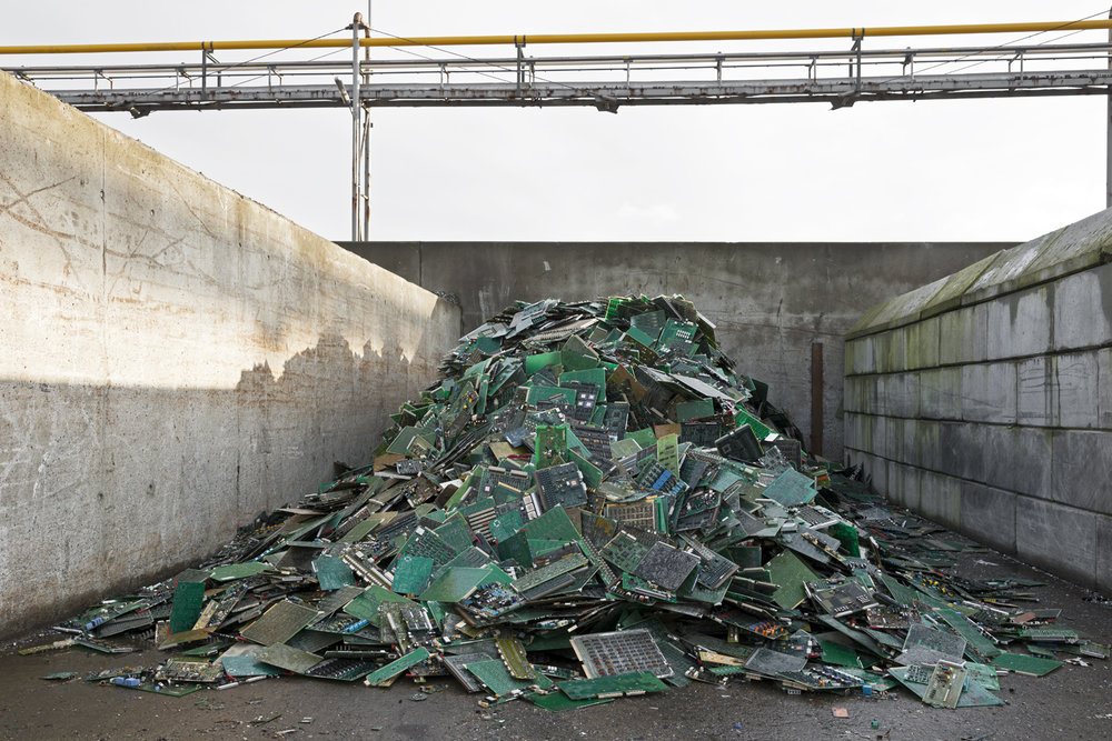 Recovered circuit boards. The finely shredded circuit board are melted in an oven in which the plastic carrier of the circuit boards contributes to the fuel. After a number of processes, metals such as gold, silver, platinum, lead, copper, tin, nickel, and tellurium are recovered.  Inquire about this image