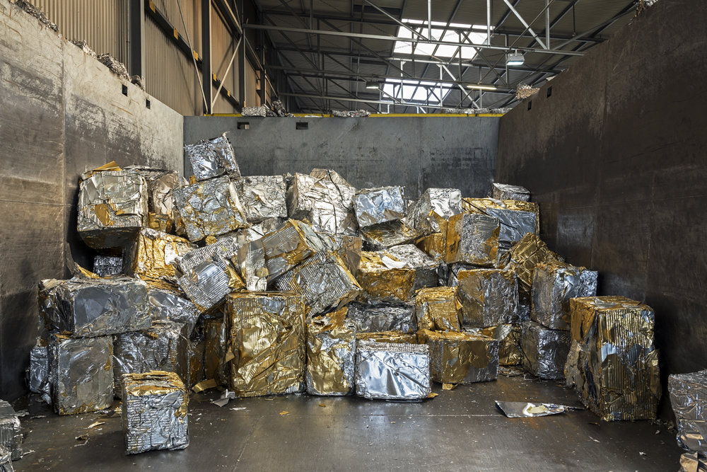 Blocks of compressed aluminum scrap. Each block weighs approximately 200 kg and contains a small quantity of gold-colored lacquer typically used for beer can covers. In a specific recycling smelter, the lacquer is burnt and the molten aluminum is cast into new blocks that can be used to produce new cans, among other things.  Inquire about this image