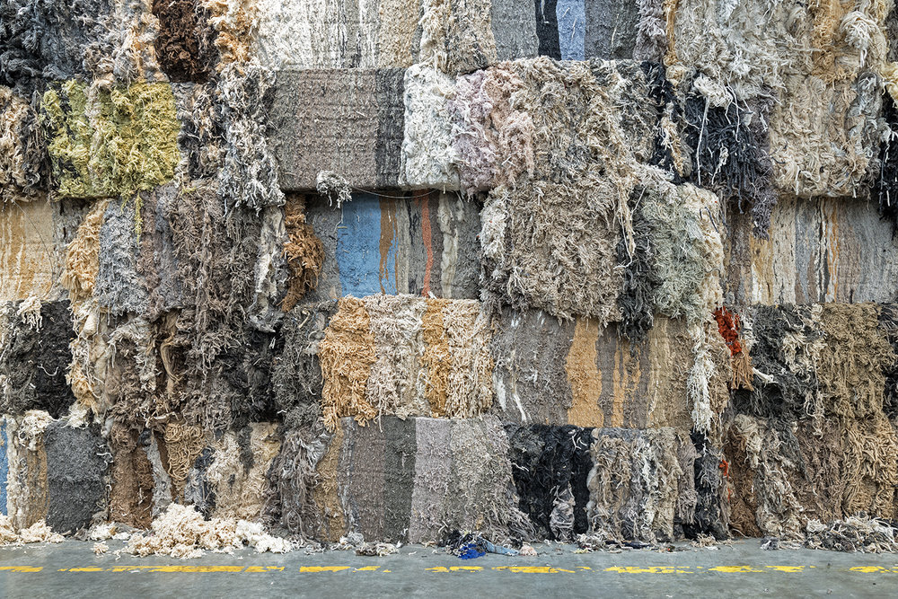 Bales of scrap wool from the carpet industry. This material will be cut and unraveled for reuse in the production of heat-resistant felt. This recycled fiber can also be spun into yarn.  Inquire about this image