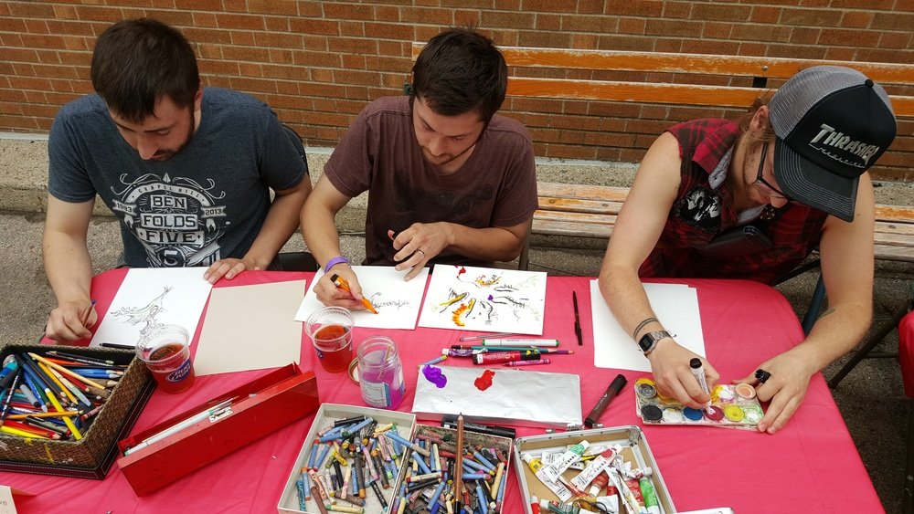 Luke Crowe draws with a couple of friends who spontaneously joined in the effort at the Drawing Rally.