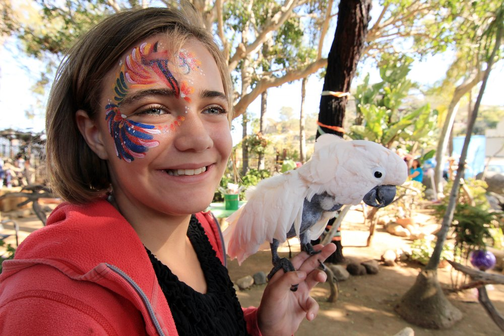 "Junior Docent Mia with ""Peanut,"" the Moluccan Cockatoo"