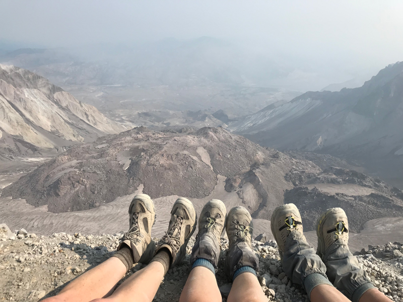 Our weary dusty feet at the top of the volcano, looking into the crater.