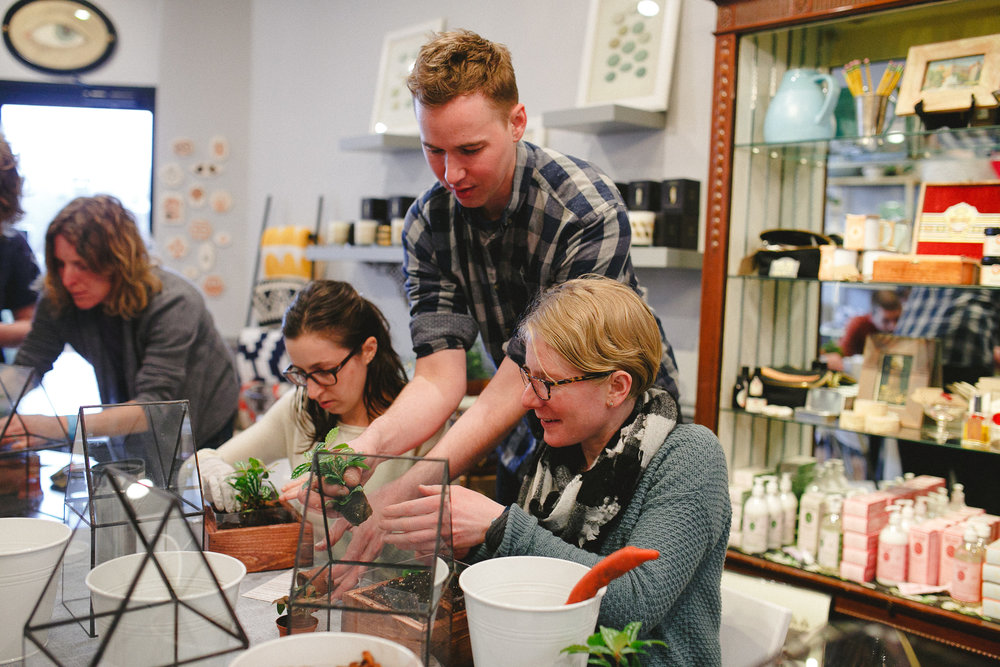 Chad Ackley, one of the owners of Lead Head Glass, leading a terrarium planting workshop at the shop.  Photo by Abby Rose Photography