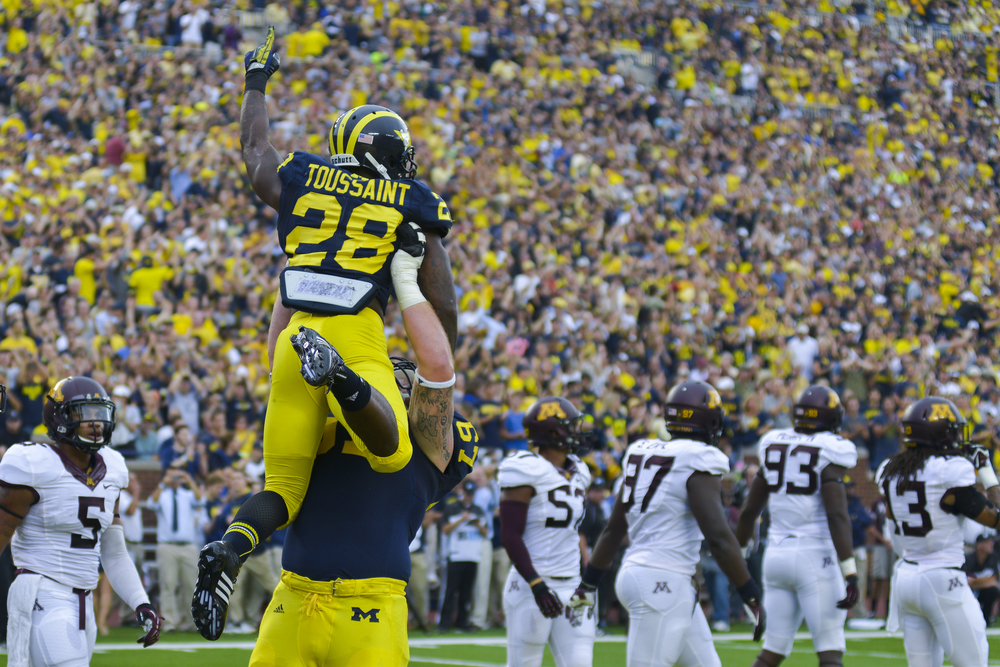 Michigan RB #28, Fitz Toussaint celebrates with teammate OL #67 Kyle Kalis after scoring a touchdown against Minnesota. Toussaint ran for 78 yards and two touchdowns, the Wolverines went on to win 42-13.