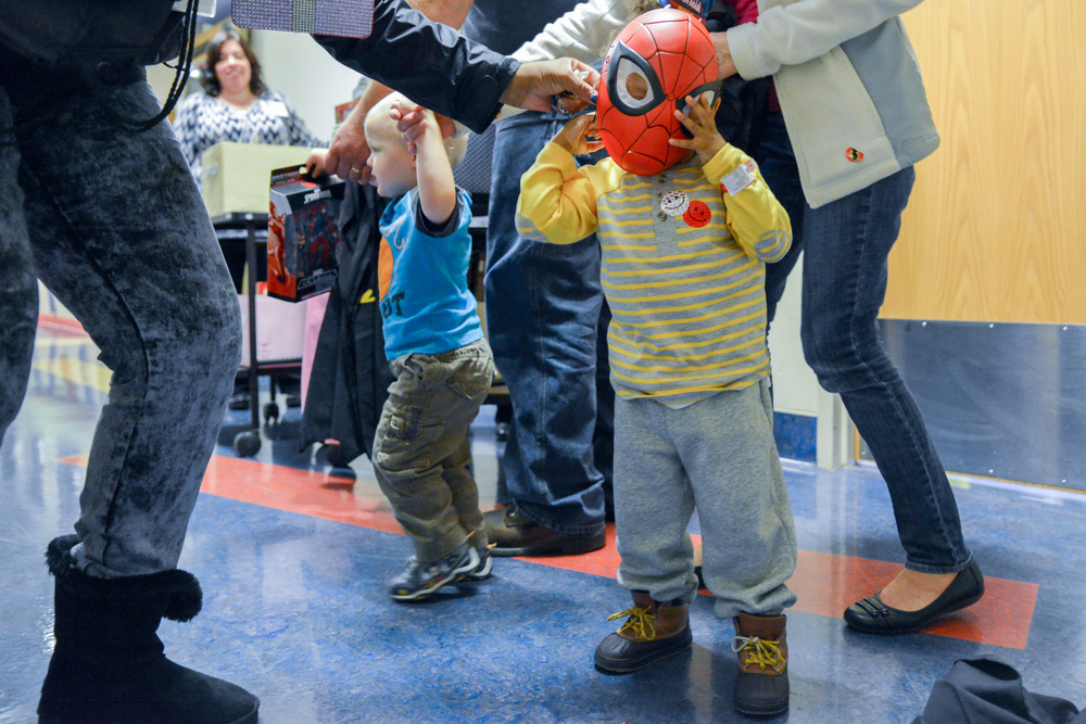 Demeir, 2, tries on his new mask after meeting Spiderman at Children's National.