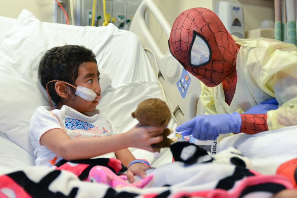 "The Hope for Henry Foundation hosted a Superhero Extravaganza at Children's National. In honor of the late Lenny ""Batman"" Robinson, 15 superheroes visited children in the Oncology Department and delivered superhero toys on Wednesday October 21, 2015 in Washington, DC. Christina, 8, shows Spiderman her favorite stuffed monkey, Coconut and later her stuffed panda, Bamboo."