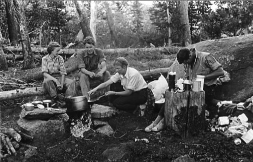 Patsy English, David Brower, Virginia Adams and Jules Eichorn cooking a meal in their camp, 1930's. Photograph by Ansel Adams.