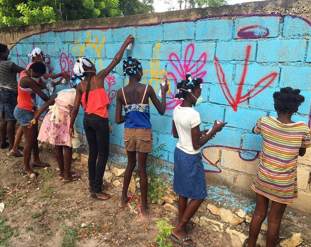 A group of Haitian girls with the Lide Foundation paint their own version of David Choe's Munko.