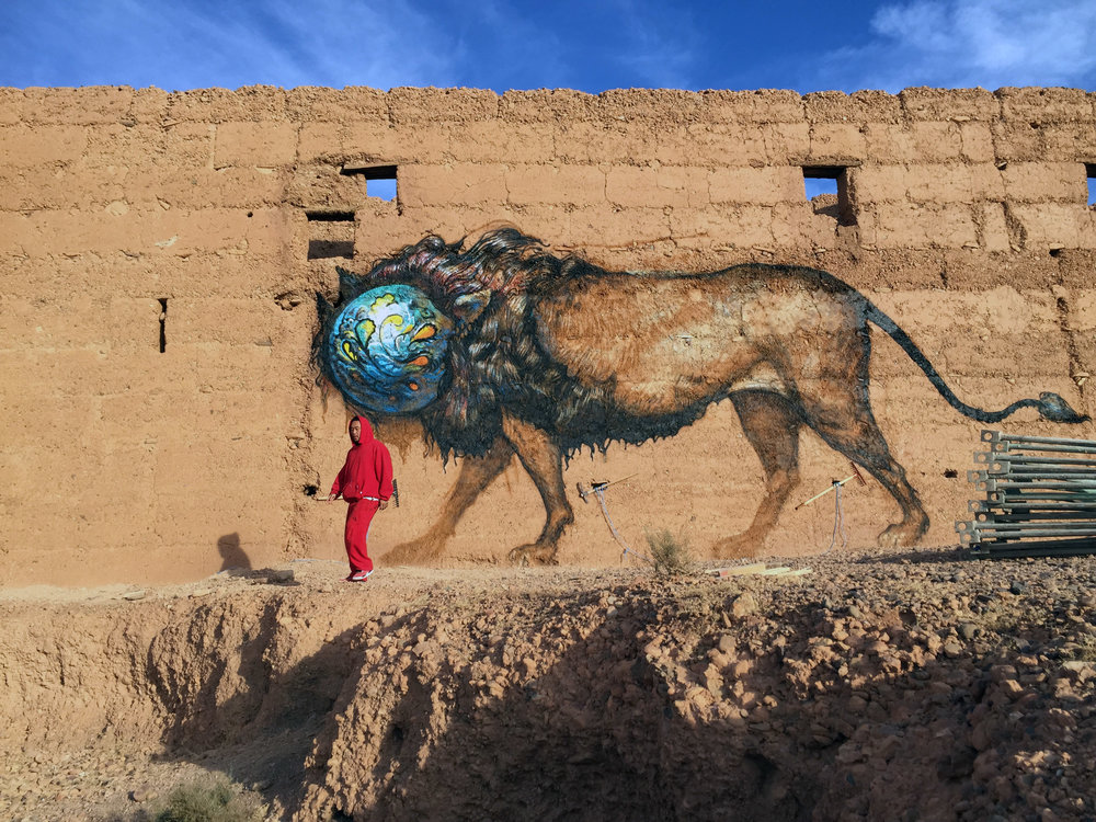 David Choe in front of a mural by artist Esao Andrews for the Igloo Hong art project in Adgz, Morocco, 2016
