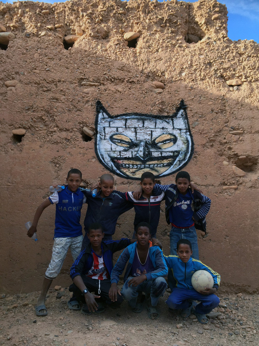 Kids in front of a mural by David Choe for Igloo Hong art interventions in Adgz, Morocco, 2016