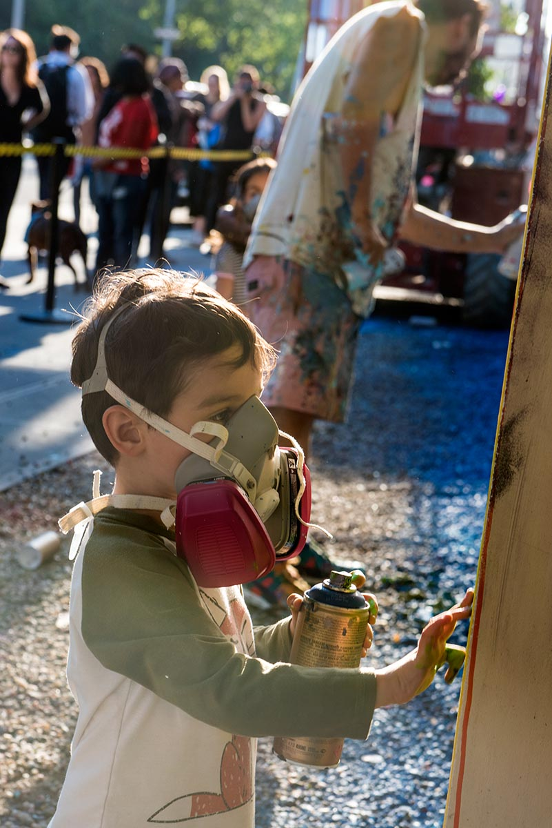 Young child painting alongside artist David Choe at the Bowery graffiti wall in New York. Photo by Martha Cooper.