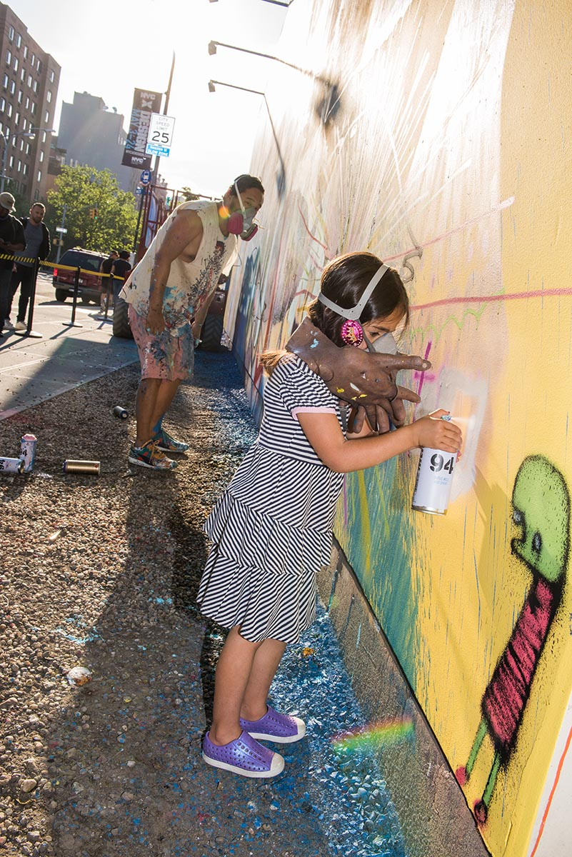 Young girl painting alongside artist David Choe at the Bowery graffiti wall in New York. Photo by Martha Cooper.