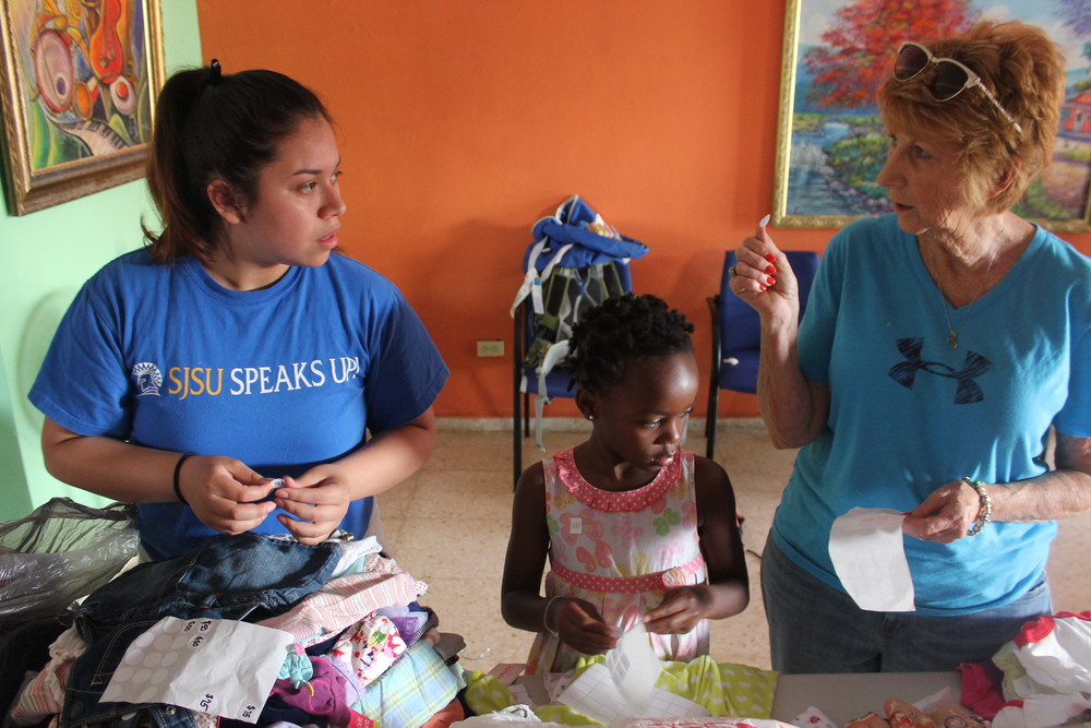 Valerie, a helper, and Anne putting price stickers on the clothes.