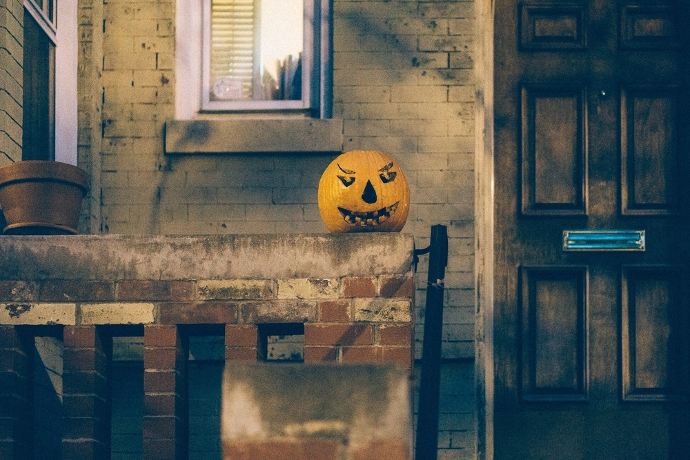 Tardy Jack O'Lantern rotting on a stoop.