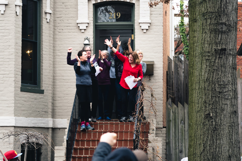 Women come out on their stoop to greet and cheer on protestors marching down 3rd St NE, in the Capitol Hill neighborhood.